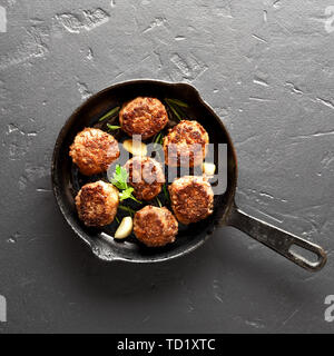 Fried cutlet in frying pan over black stone background. Top view, flat lay - Stock Image