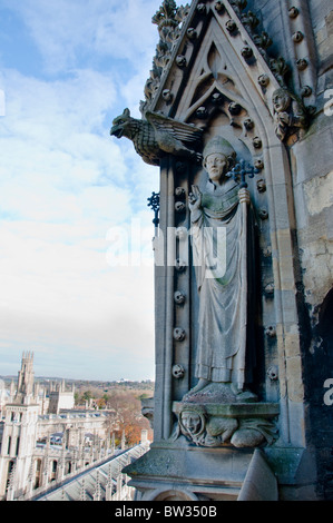 Carved ornament high above on the spire of the church of St Mary the Virgin with All Souls College down below, Oxford, - Stock Image