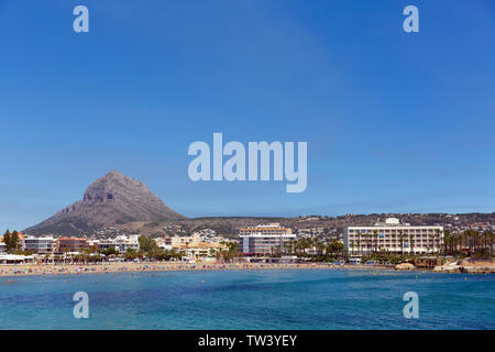 Xabia Spain Playa del Arenal beach in summer with mountain view hotels and blue sea and sky - Stock Image