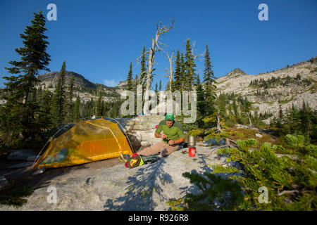 Distant view of a man making coffee near a camping tent, Selkirk Mountains, Sandpoint, Idaho, USA - Stock Image