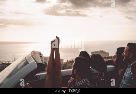 Happy friends driving on convertible car at sunset - Young people having fun during vacation road trip in cabriolet - Stock Image