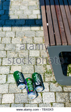 Three empty Carlsberg beer cans laying on the - Stock Image