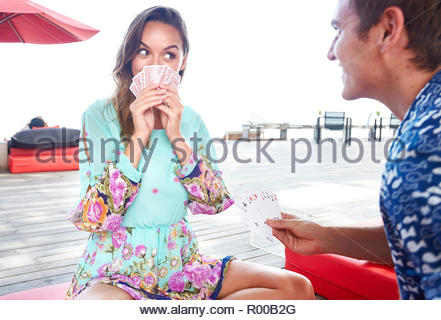 Young couple playing cards on deck - Stock Image