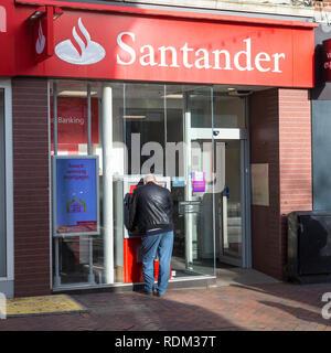 A man at a cash point, santander bank, ashford, kent, uk - Stock Image