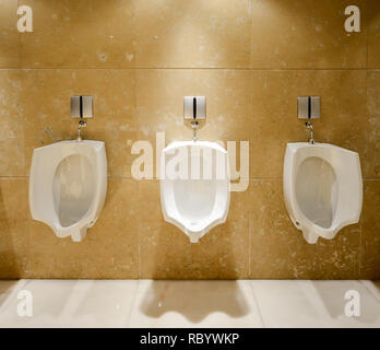 A row of urinals in tiled wall in a public luxurious restroom - Stock Image
