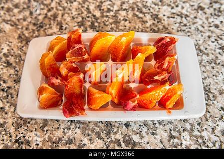 orange slice in plastic container resting on the granite table - Stock Image