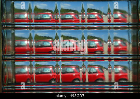 Abstract view of a red car seen through a glass brick. - Stock Image