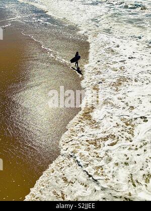 Surfer walks down the beach. Manhattan Beach, California USA. - Stock Image
