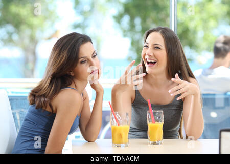 Bored woman suffering a bad conversation from a friend in a coffee shop or hotel on the beach - Stock Image