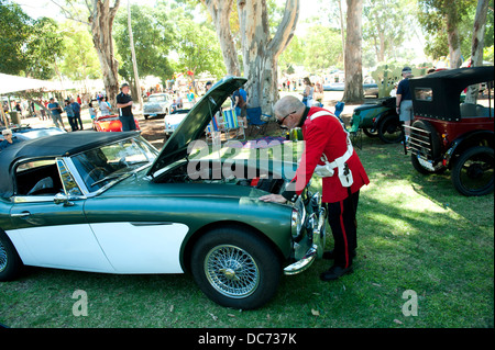Man in period military costume inspecting motor of classic Austin-Healey 3000 sportscar. - Stock Image