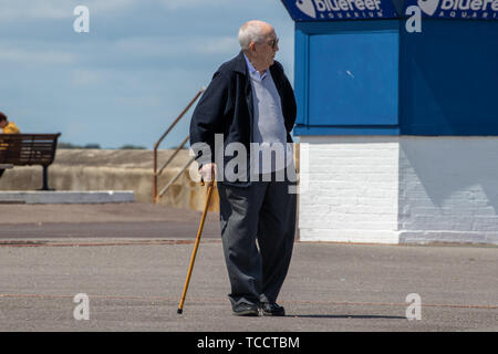 An elderly man walking with a walking stick or a cane - Stock Image