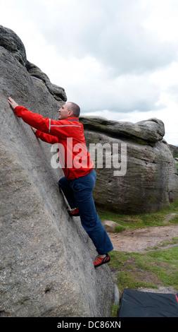 rock climber Doug Blane bouldering at Burbage Edge South, Derbyshire, Peak District National Park, England, UK - Stock Image