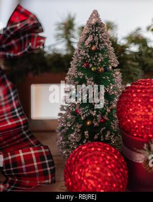 Closeup of tabletop Christmas decor. Christmas tree, red balls, plaid ribbon, garland. USA - Stock Image