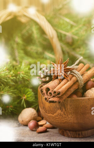 Winter spices and ingredients for cooking the Christmas meal. Cinnamon sticks, hazelnuts, walnuts,  anise stars, Christmas tree branches on  old woode - Stock Image