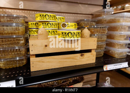 Containers of natural comb honey for sale in a store - Stock Image