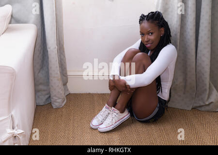 Pretty young woman in denim shorts and white top sitting on the floor - Stock Image