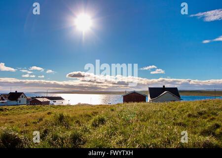 The bright summer sun is illuminating the village Ekkerøy at Varangerfjorden in arctic Norway. - Stock Image
