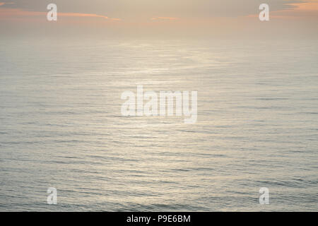 The open ocean, water surface calm and grey and the glow of the sun at dawn on the horizon. - Stock Image