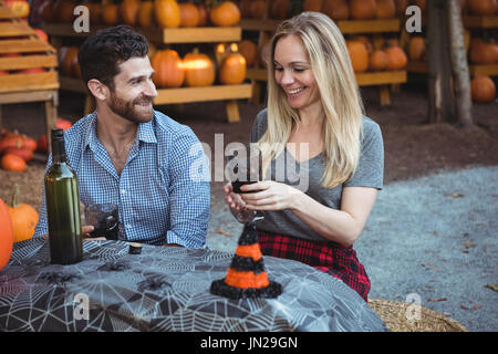 Couple interacting while having a glass of wine - Stock Image