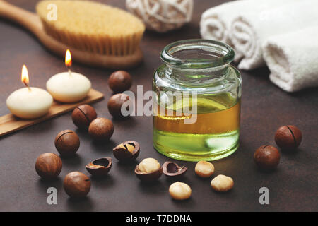 macadamia oil in a glass bottle, macadamia nuts, objects for spa on a brown background - Stock Image
