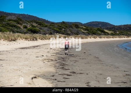 Hiker on beach viewed from behind in the Freycinet National Park, Tasmania on a summer day with blue sky - Stock Image