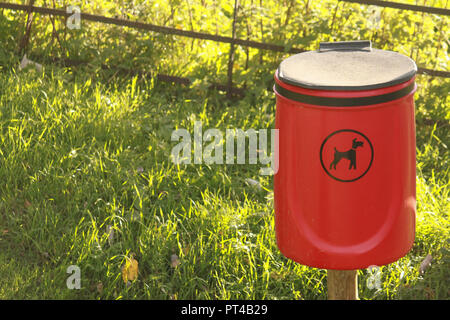 Red dog waste bin in the countryside - Stock Image