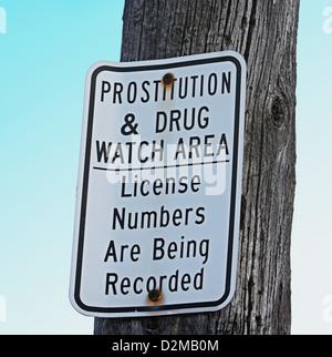 prostitution and drug trafficking sign on telephone pole - Stock Image