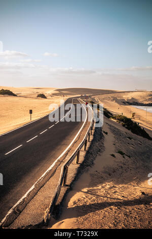 Long black way road in the desert with beautiful beach on the side - concept of travel and summer adventure alternative vacation in tropical beautiful - Stock Image