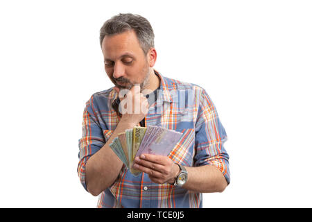 Man with curious expression looking at cash money in hand and counting isolated on white studio background - Stock Image