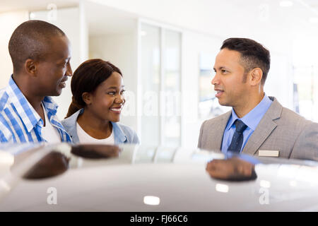 young African couple buying new car at dealership - Stock Image