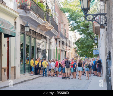 Tourists on a street in the old district of Havana. - Stock Image