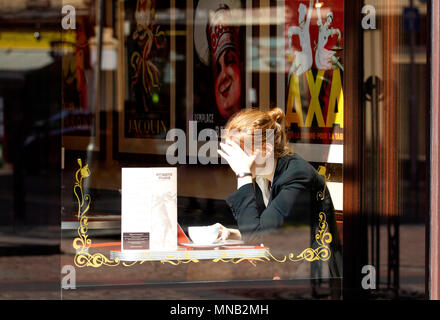 A young blonde woman sitting inside the Cordially Cake Cafe using her laptop and enjoying a cup of coffee in Dundee city centre, UK - Stock Image