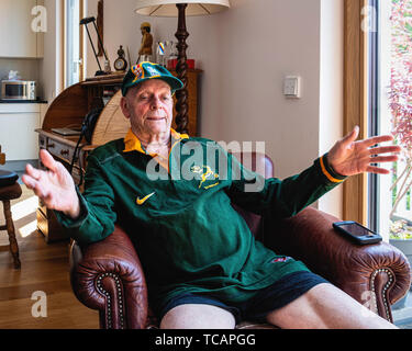South African cricket fan at home watching his team during 2019 World Cup Cricket tournament. Senior man in green & gold colours of SA team - Stock Image
