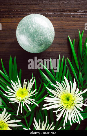 Green Aventurine Sphere with White Chrysanthemums and Foliage on Dark Wood - Stock Image