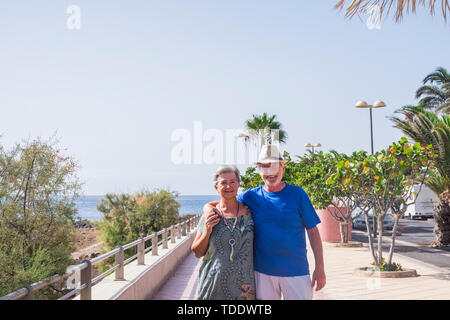 Senior couple on holidays walking near the sea in summer season - happy mature people in retired lifestyle relax outdoor leisure activity - Stock Image