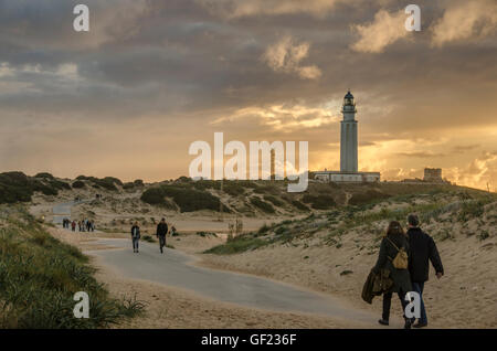 People walk amongst sand dunes towards the lighthouse at Cape Trafalgar, on the coast by the small seaside town - Stock Image