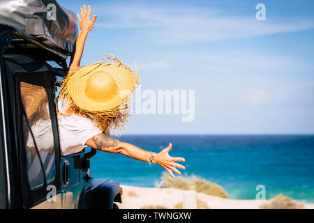 Travel and freedom concept with happiness and joy - people in summer holiday vacation - woman outside the car in front of a scenic beautiful beach and - Stock Image