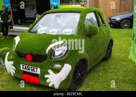 90th Kent County Show, Detling, 6th July 2019. A car covered in grass and a face advertising a gardening company. - Stock Image
