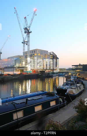 View of cranes for construction of the new Google HQ across the Regents Canal at Kings Cross, at dusk, in spring weather, in London, UK - Stock Image