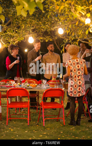 Friends talking under trees at dinner garden party - Stock Image