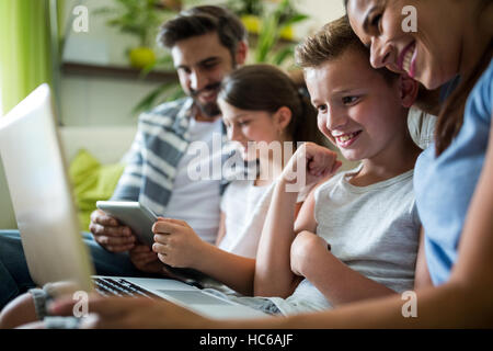 Happy family using laptop and digital tablet in the living room - Stock Image
