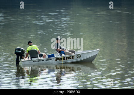 Two Allegheny county police officers in a motor boat patrolling North Park lake, Pittsburgh, Pennsylvania, USA - Stock Image