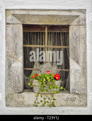 AT - TYROL: Old stone window with flower basket at Rattenberg on Inn - Stock Image