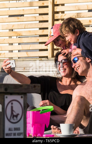 A happy family of holidaymakers taking a selfie with an iPhone at a sunny Fistral in Newquay in Cornwall. - Stock Image