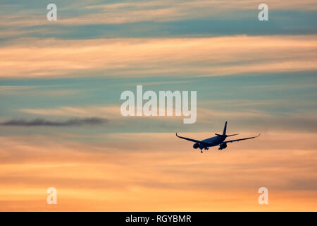 Airplane taking off in the sunset - Stock Image