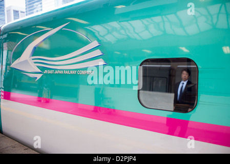 Reflection of a business man waiting for a shinkansen bullet train in Tokyo Station Tokyo Japan - Stock Image