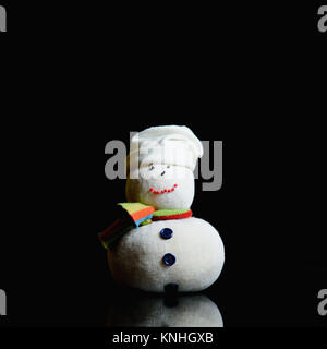 Snowman figure on black background. He has stocking cap, eyes, mouth and nose made with beads, shawl, buttons on - Stock Image