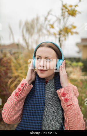 Smiling woman listening to music with headphones outside - Stock Image