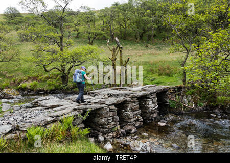 Walker Crossing the Old Slate Bridge over Trout Beck Below the Hill of Troutbeck Tongue, Lake District, Cumbria, UK - Stock Image