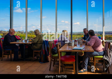 People enjoying afternoon tea at window seats in the Abbey View Café with views across Whitby to the Abbey - Stock Image